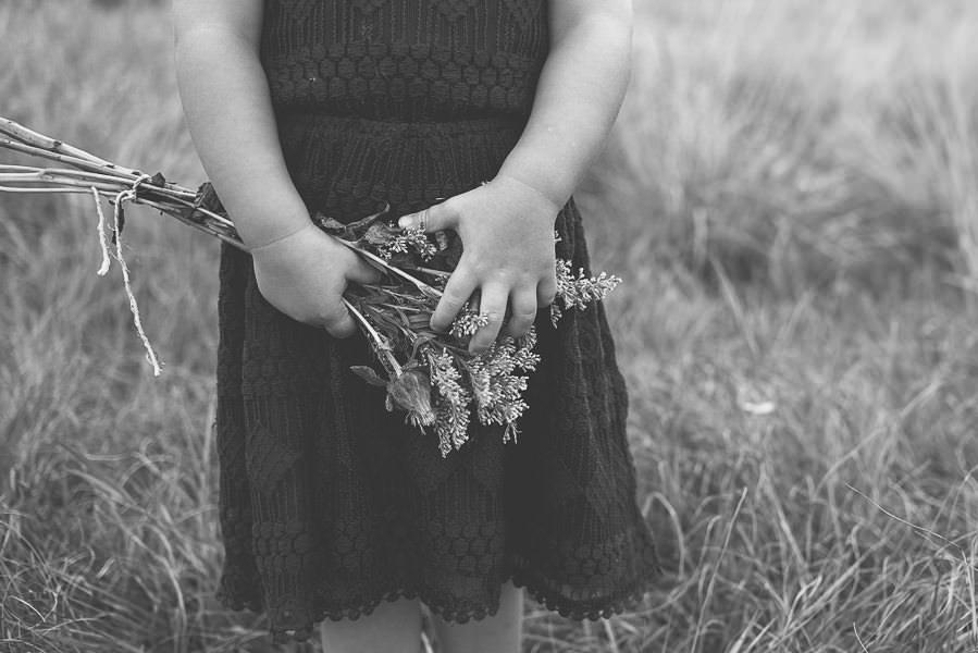 little girl holding flowers in field