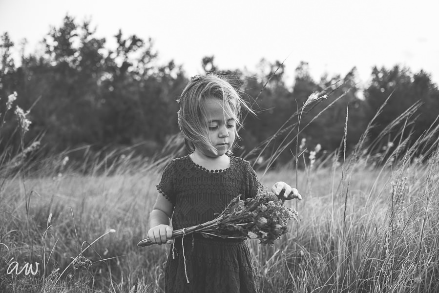 little girl with flowers in field