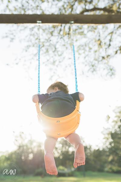 little boy in swing with sun setting
