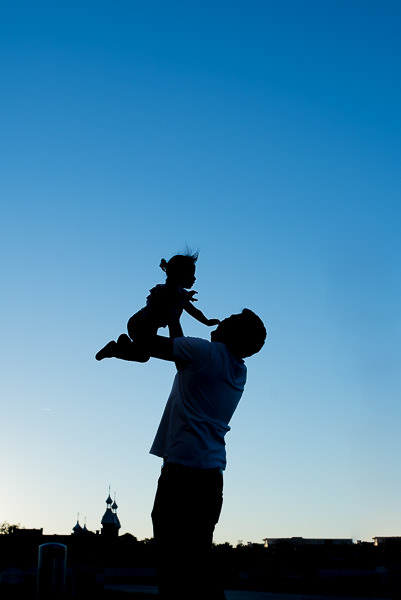 Silhouette of a father and his daughter in front of the University of Tampa in Curtis Hixon Park.