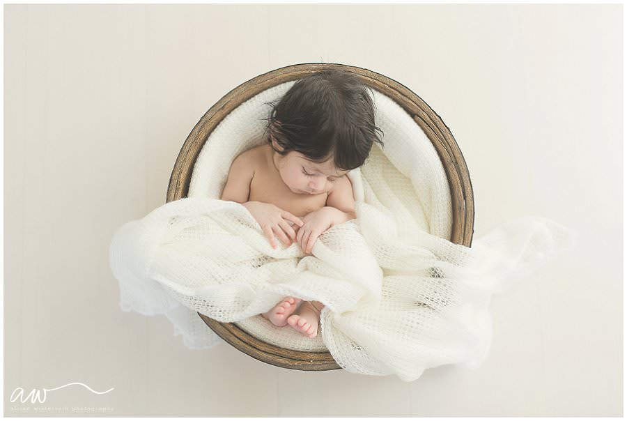 newborn baby from above in a bucket with white wrap.