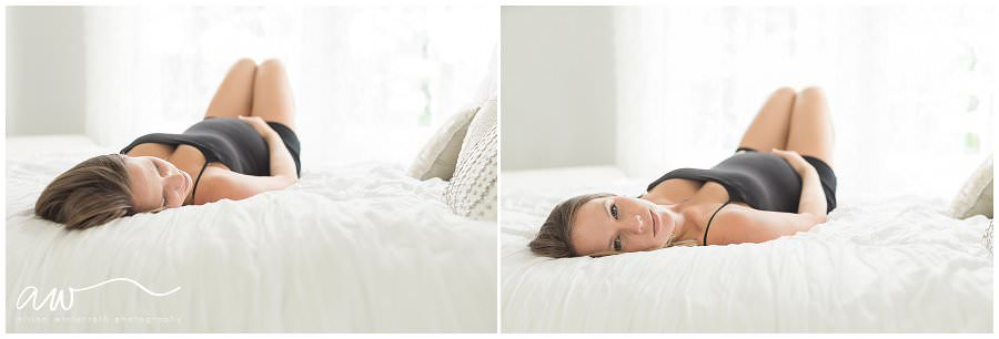 A mom on an all white bed in a natural light studio.