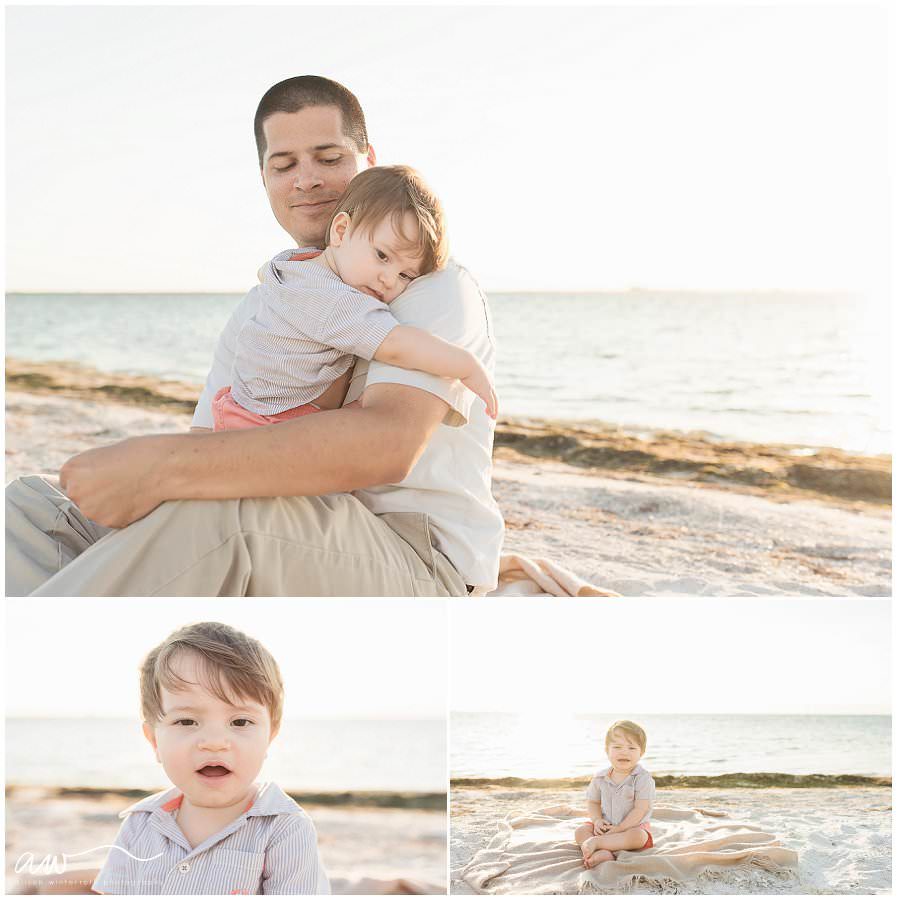 One year old boy snuggling with his dad at at the beach.