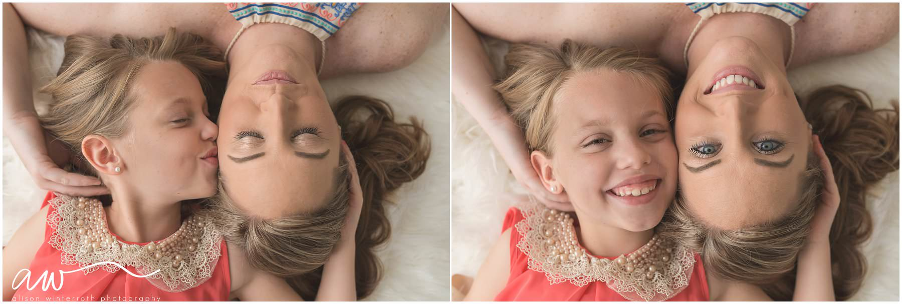 A mom and her daughter laying on a rug holding each other