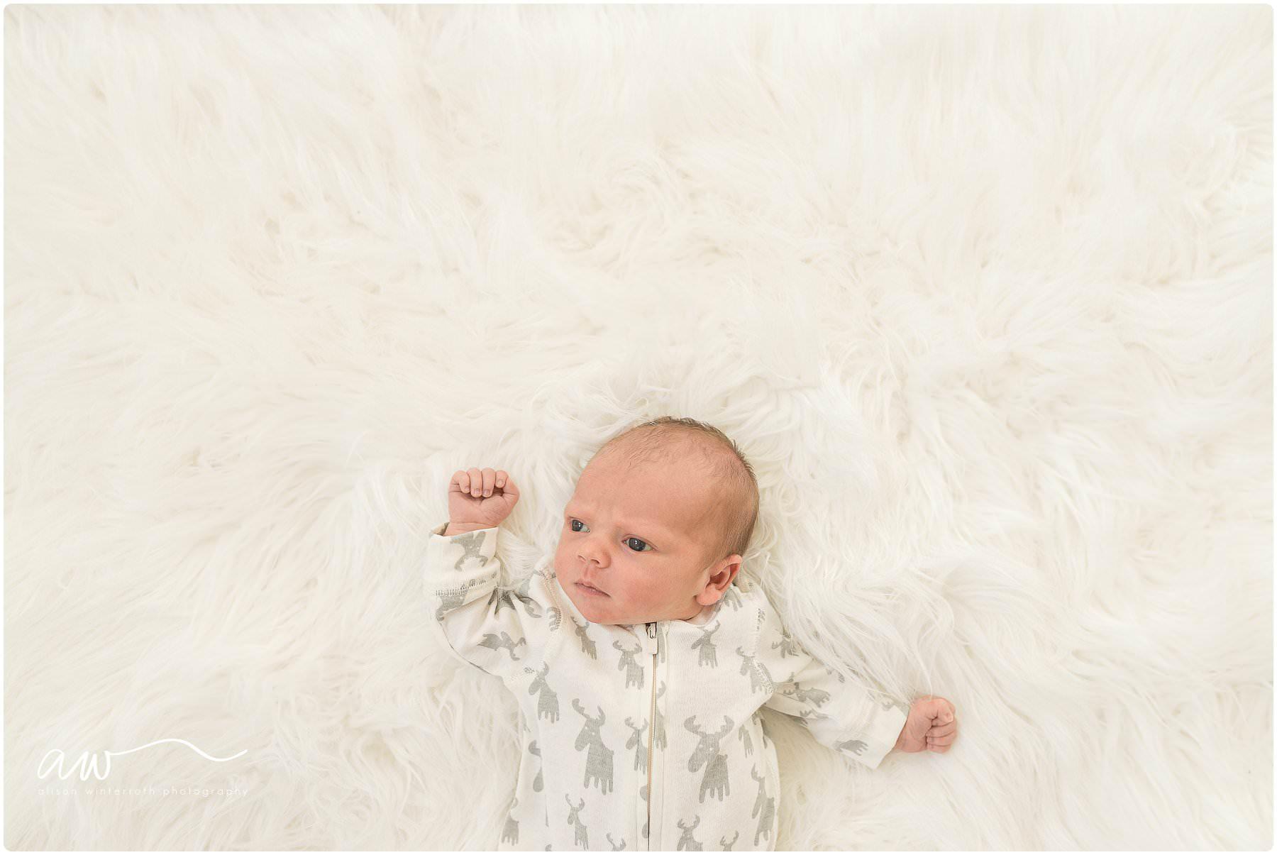 A newborn baby looks around on a white fur blanket
