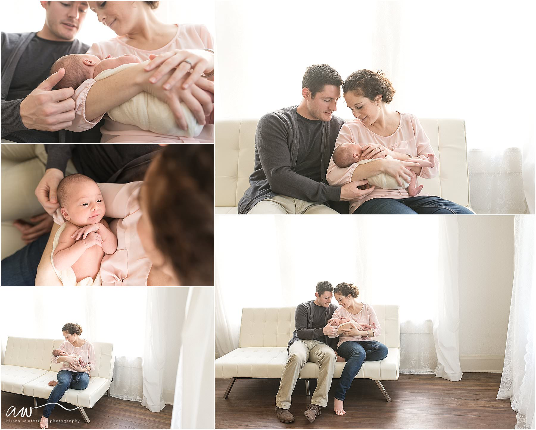 A mother and father hold their new baby girl on a white couch.