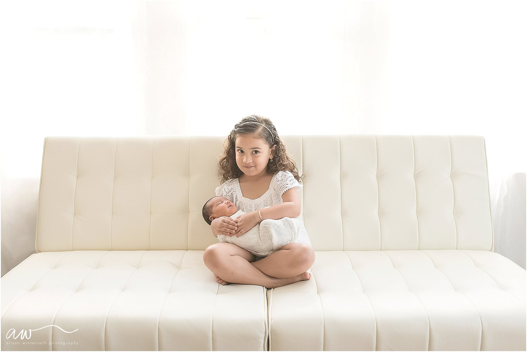 A big sister holds her baby sister on a white couch.