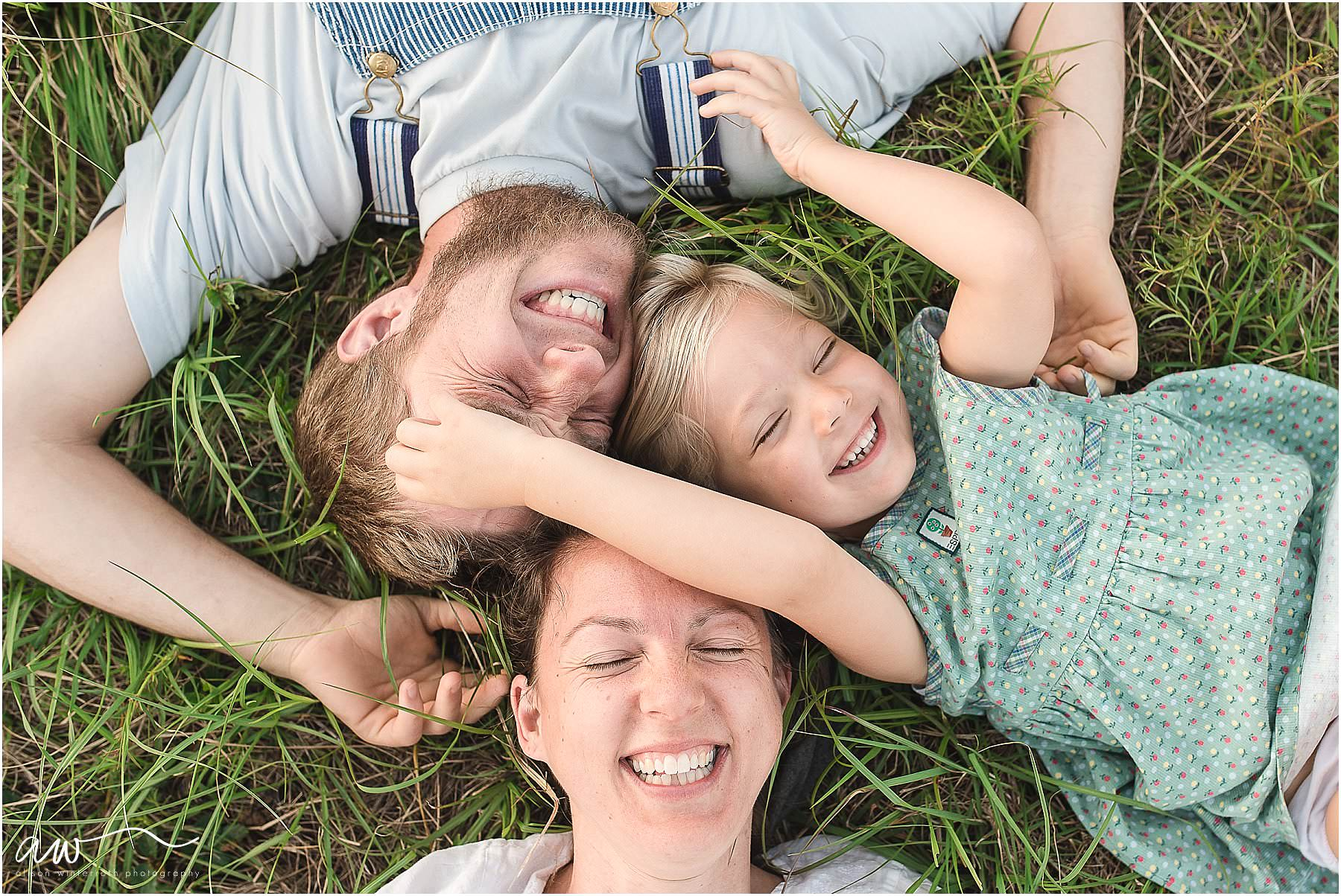 family of three from above laughing