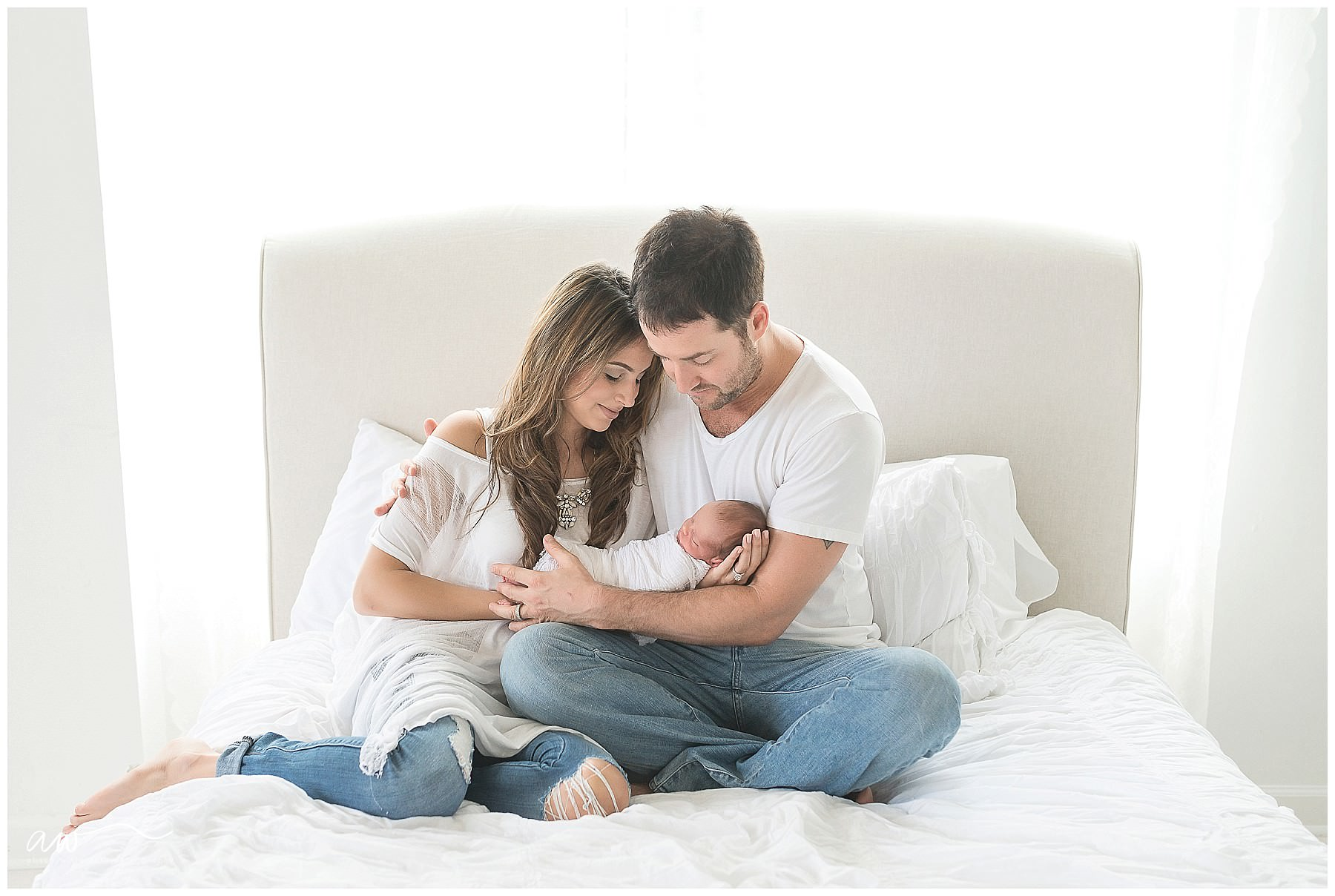 a couple holding their newborn baby on a bed