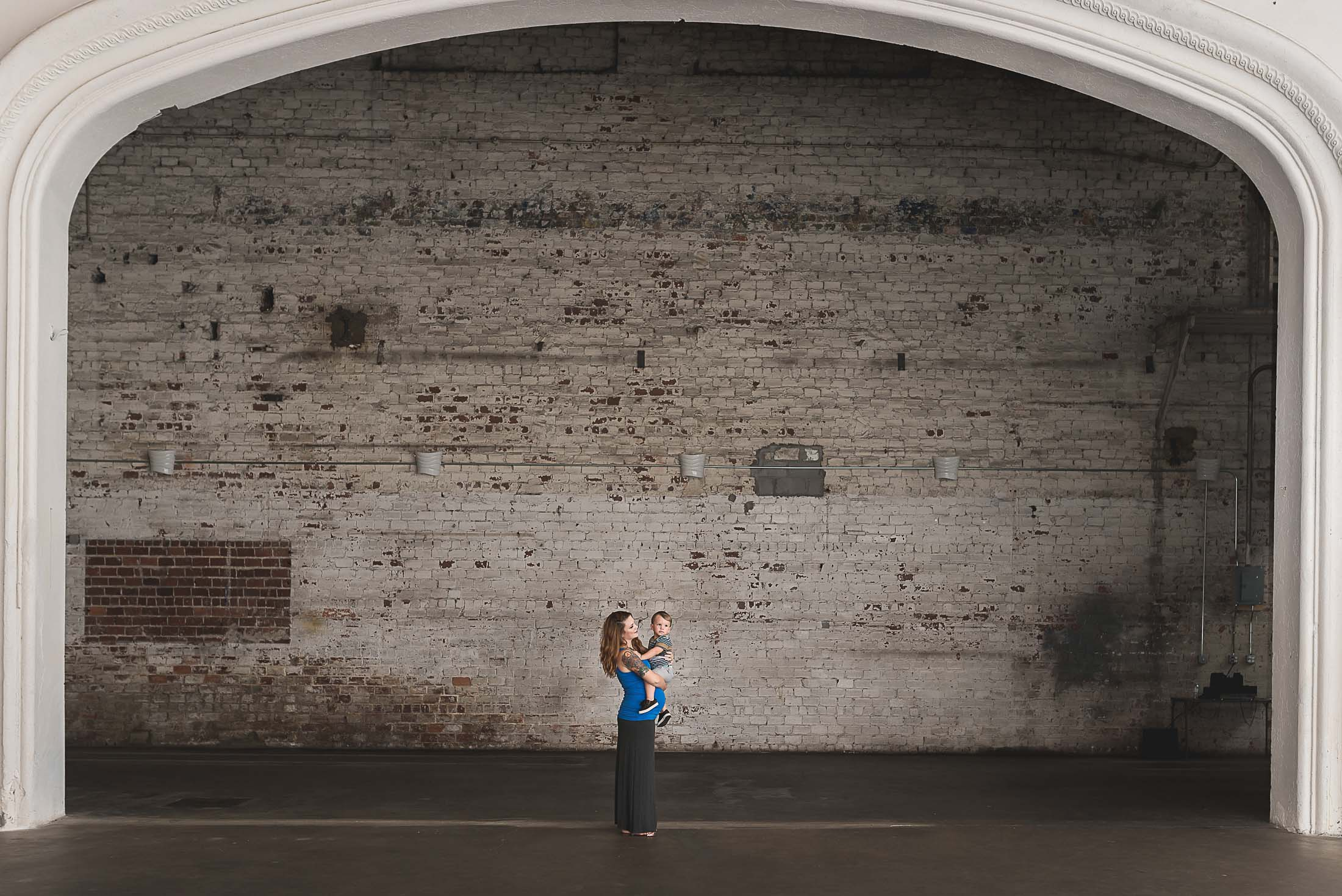 A pregnant woman in front of an exposed brick wall in the Rialto Theatre