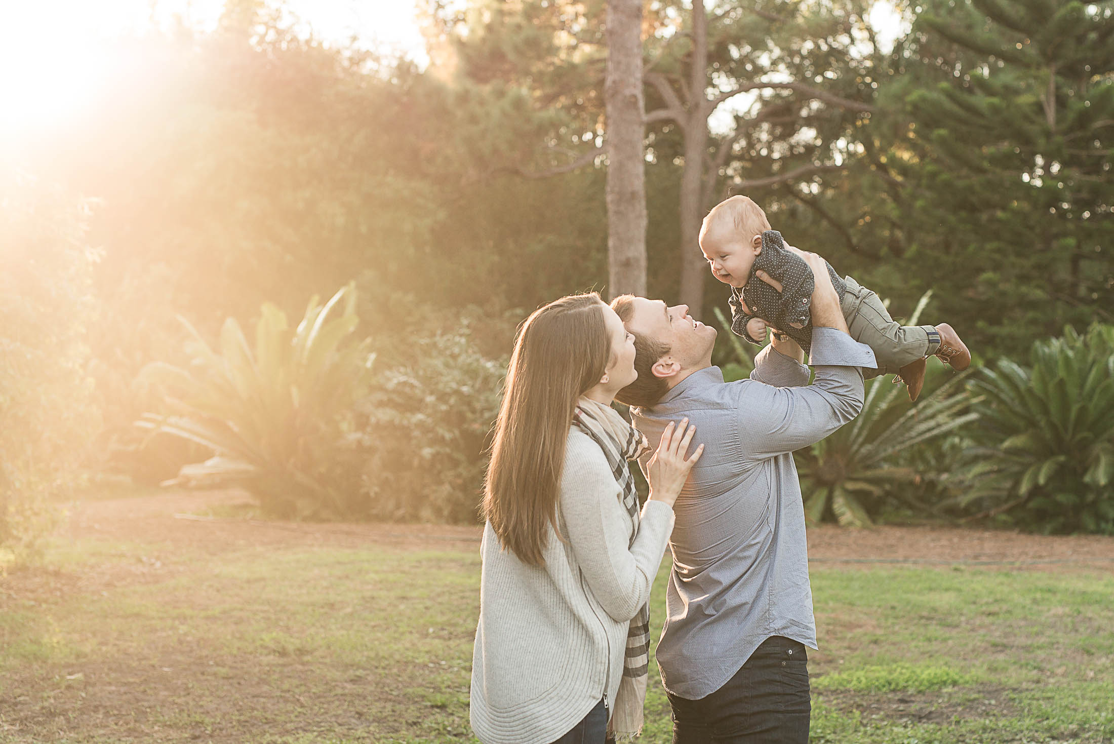 family of three holding their son at USF botanical gardens